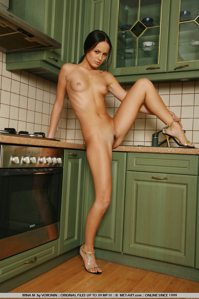 Young wife with petite body is breaking in her new kitchen and adding some spices.
