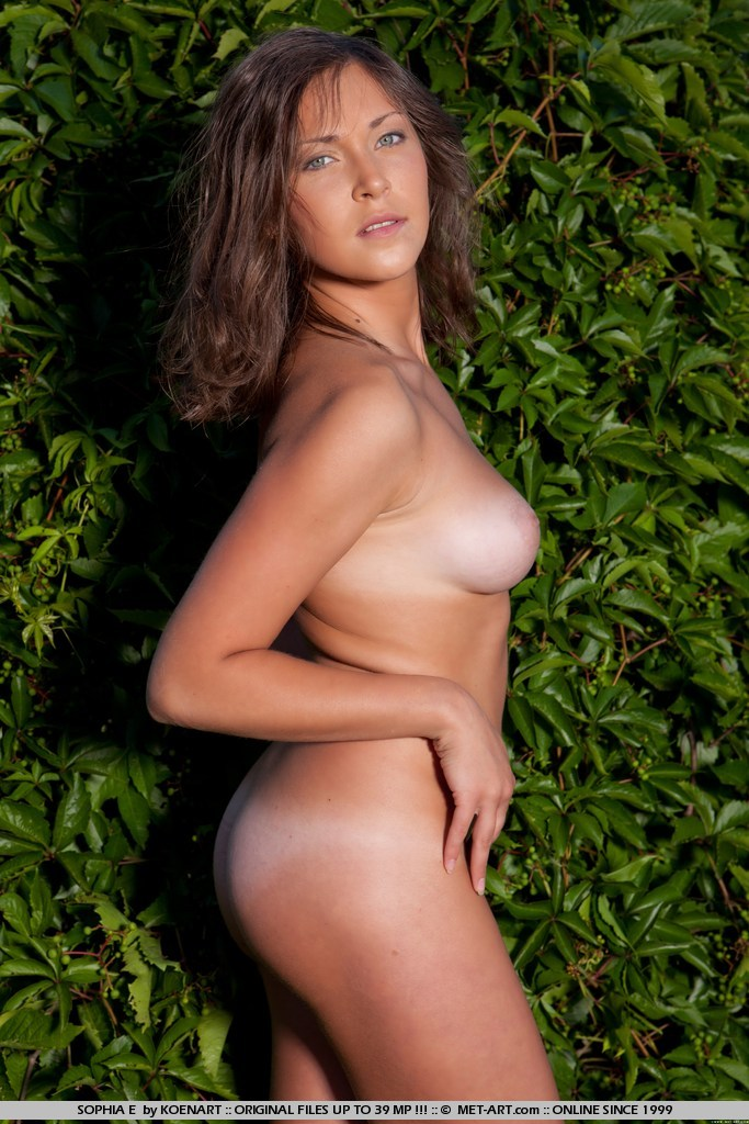 Tanned brunette with erotic poses against the green, leafy background.