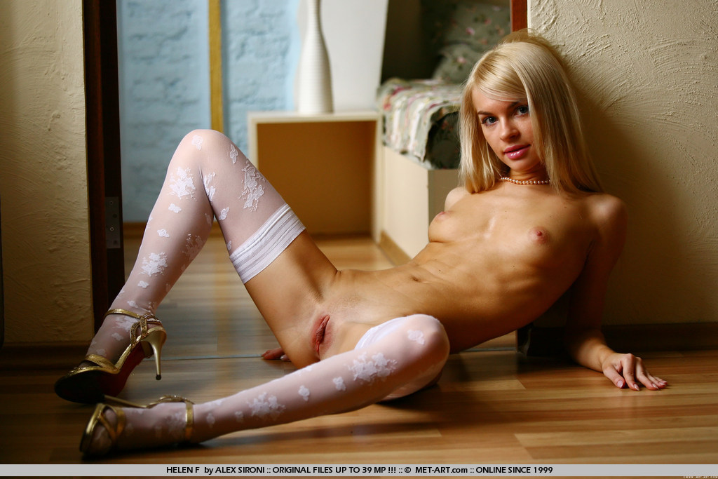 Pristine young girl with blue eyes and soft blonde hair slowly removes her all white top and bottoms.