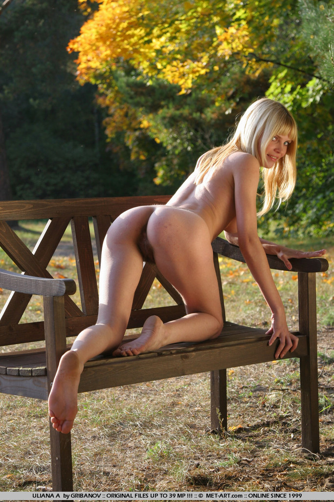 Golden blonde at sunset outside on the bench in the autumn colors.