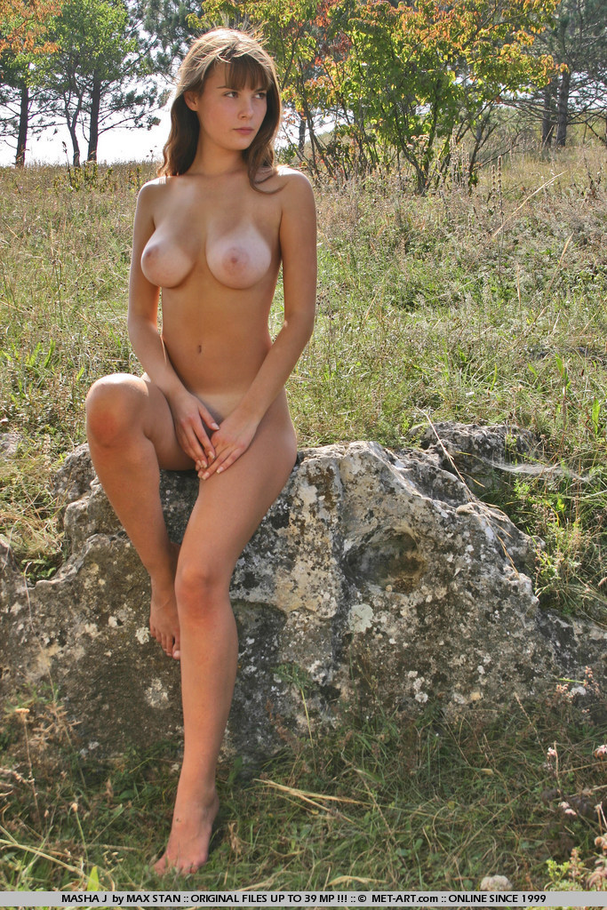 Suntanned beauty is caught sunbathing in a secret field.